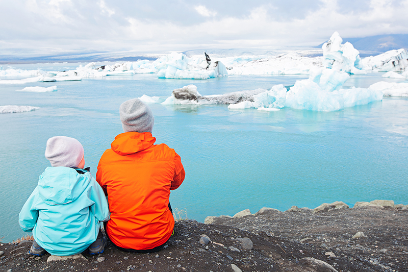 Father and Son in Patagonia looking at icebergs