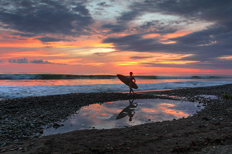 Surfer on beach at dusk in Costa Rica